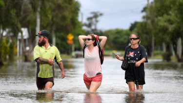Local residents wade through flood water  in Townsville, Queensland, in February this year.