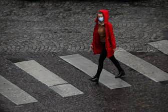 A woman crosses a quiet Paris street on Tuesday. France is under an extended stay-at-home order until May 11.