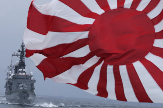 The Japanese escort ship Kurama, left, navigates behind destroyer Yudachi, carrying a rising sun flag - the kyokujitsuki -, during a fleet review off Sagami Bay, south of Tokyo, in 2012.