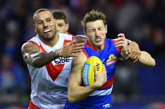 Lance Franklin tackles the Bulldogs' Bailey Dale during Sydney's win on Sunday.