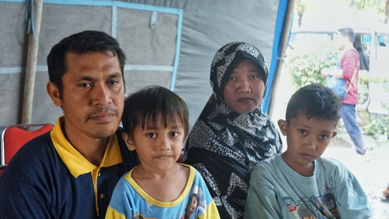 """Amirudin U. Labugis (left) and his family after his house was swept away in a """"tsunami of mud"""" following the earthquake in Sulawesi."""