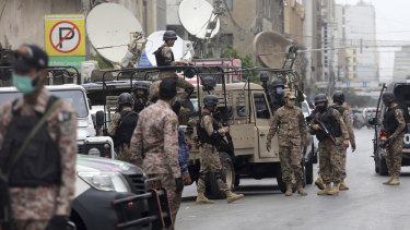 Security personnel surround the stock exchange after an attack in Karachi, Pakistan.