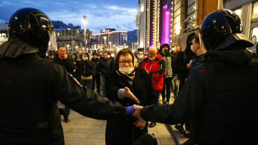 A woman gestures in front of riot police blocking traffic during the opposition rally in support of jailed opposition leader Alexei Navalny.