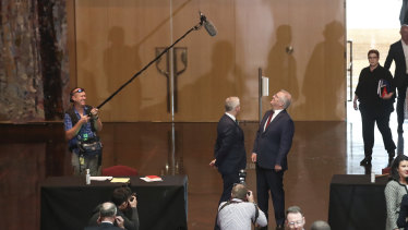 These are not the days for careless words ... Deputy Prime Minister Michael McCormack and Prime Minister Scott Morrison clam up after spotting the boom microphone above them.