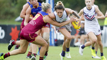 Dangerous player: Kate McCarthy lays a tackle on Melissa Caulfield.