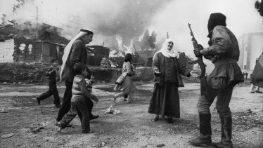 A Palestinian woman pleads with a Christian militiaman in Beirut while a man tries to take children to safety during the Lebanon war in 1976.