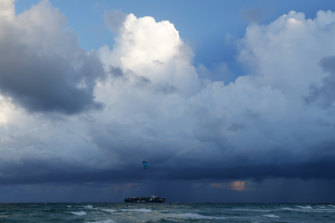 A container ship heads out to sea into bands of rain as a kitesurfer enjoys the winds off South Beach, Friday. All of Florida is under a state of emergency ahead of Hurricane Dorian.