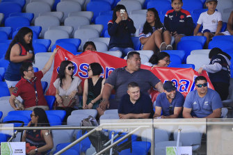 Deregistered player agent Isaac Moses (in blue shirt and black cap) sitting with the Suaalii family on Saturday.