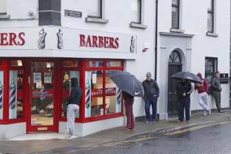 People queue outside a barber's shop in Athy in the Irish county of Kildare after restrictions were eased on June 29. The county has now gone back into partial lockdown.