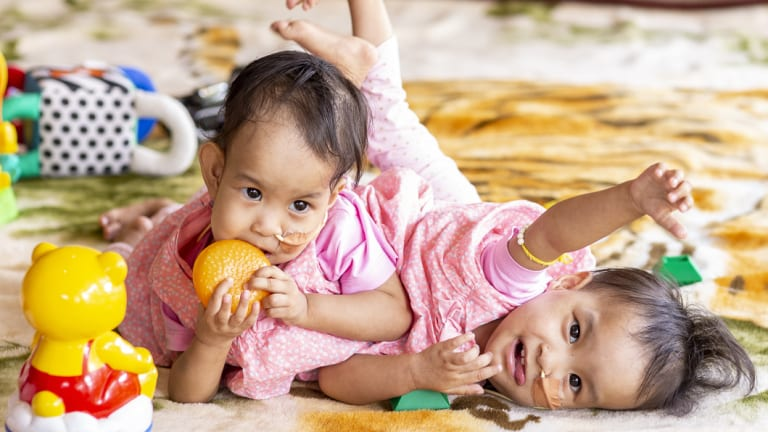 Nima (left) and Dawa play at the country retreat they have called their home for the past month.