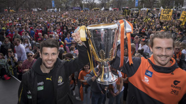Richmond's Trent Cotchin and GWS captain Phil Davis pose with the premiership cup on grand final eve.