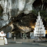 Pope John Paul II prays in front of the statue of the Virgin Mary in the grotto of Lourdes, southwestern France, in 2004.