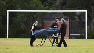 The woman's body is removed from the centre of a soccer pitch in Princes Park, Carlton North, on Wednesday.