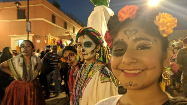 Girls take part in the traditional dances in the streets of Oaxaca during Day of the Dead parade.