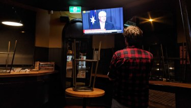 Peter Sherwood watches the prime minister's announcement from his empty front bar.