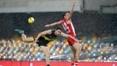 Goal drought: Richmond's Jason Castagna battles Sydney defender Jake Lloyd in a game that saw just seven majors scored at a wet Gabba on Sunday.