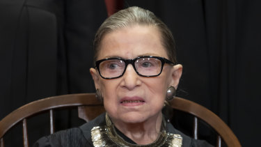 Ruth Bader Ginsburg sits with fellow Supreme Court justices for a group portrait at the Supreme Court Building in Washington.