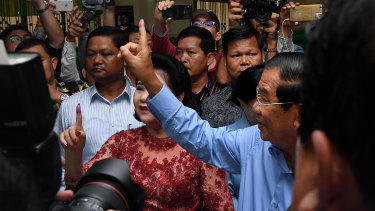 Hun Sen (right) raises his finger indicating he has voted in the Cambodian general election.