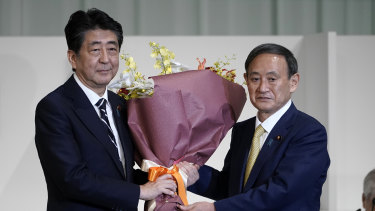 Yoshihide Suga (R) presents flowers to his predecessor Shinzo Abe after Suga was elected as new head of Japan's ruling party in September.