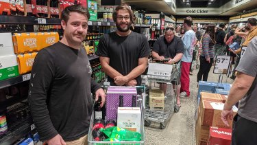 Housemates Jai Ashman and  Simon Giacomo, both 31, in line at the bottle shop on Sunday evening.
