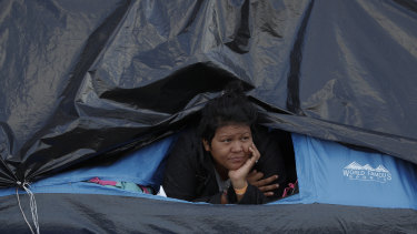 A woman rests inside a tent on the street near a sports complex shelter as authorities tried to persuade migrants to move to a new, more distant shelter, in Tijuana, Mexico, on Saturday.