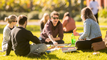 People enjoying the sun in Carlton Gardens which have been designated as an entertainment area over summer.