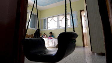 Muna Awad sits with her children in her daughter Aisha's room at the family house in Bureij refugee camp in Gaza.