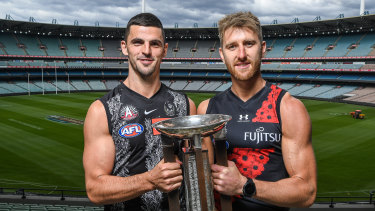 Collingwood captain Scott Pendlebury and Essendon skipper Dyson Heppell at the MCG on Monday with the Anzac Day trophy.