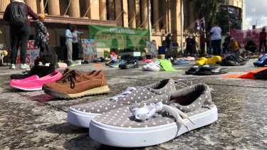 Hundreds of pairs of children's shoes laid out outside City Hall for an Extinction Rebellion protest