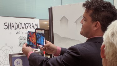Brisbane Powerhouse artistic director Kris Stewart demonstrating the augmented reality aspect of the Shadowgram installation ahead of Curiocity Brisbane.