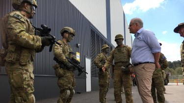 Scott Morrison meets ADF personnel at the Redbank military vehicle centre on Sunday, but Deb Frecklington was nowhere to be seen.