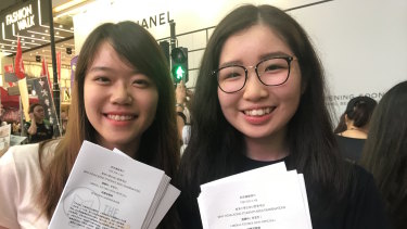 Nicole Ng, 18, and Christine Chao, 20, hand out flyers at the June 4 vigil.
