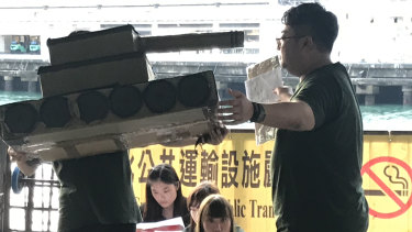 University students in Hong Kong re-enact the Tiananmen Square crackdown for evening ferry commuters.