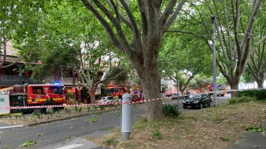 Fire crews attend to houses on Mary Street in St Kilda West as wild wind strips tin from roofs, which hit power lines.