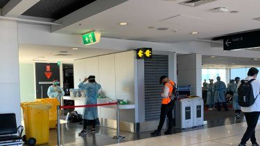 Authorities wait for the arrival of a Brisbane flight at Melbourne Airport on Saturday.