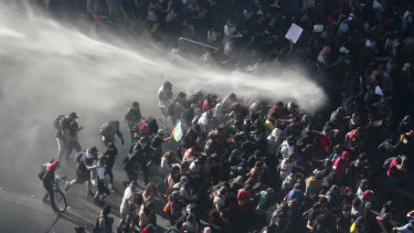 Police fight protesters with a water cannon in Santiago on Monday.