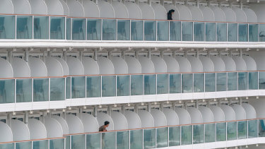 Passengers stand on balconies aboard The World Dream cruise ship as it sits moored at Kai Tak Cruise Terminal in Hong Kong, China.