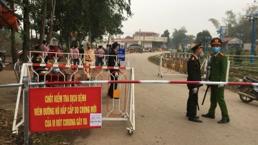 Police wearing masks guard a road checkpoint before entering the Son Loi commune in Vinh Phuc province, Vietnam.