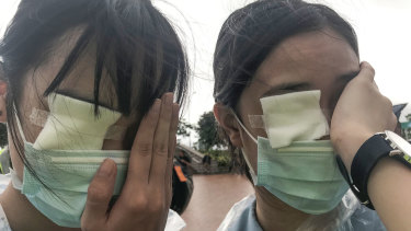 """Ezoe and Brittany, 15, at a student strike in Hong Kong, wear eye patches to remember a woman who was hit in the eye by what was believed to be a police bean bag round. They say they are protesting because they """"love Hong Kong""""."""