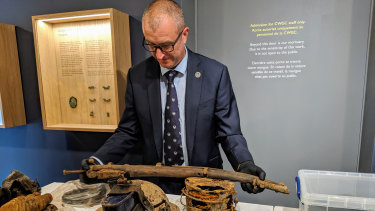 Exhumation Officer Steve Arnold shows some of the items.
