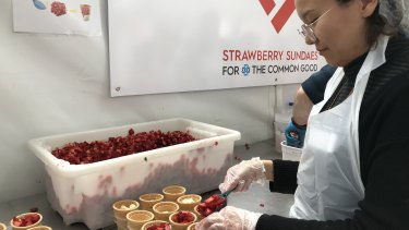 A volunteer struggles to keep up with demand for the icy strawberry treats.