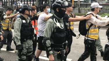 People wearing the yellow vests of volunteer group Save the Children among those arrested in Hong Kong.