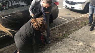 Lydia Abdelmalek's mother trips and falls outside court and is helped up by her daughter's lawyer John Yianoulatos.