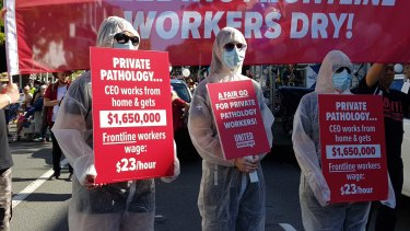 Pathology staff don hazmat suits for the Labour Day march in Brisbane.
