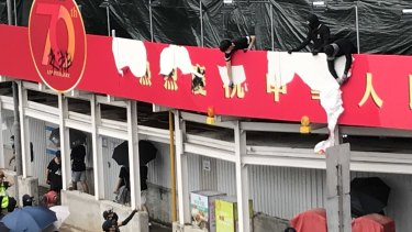 Protesters tear down a newly erected red banner celebrating the 70th anniversary of Communist China.