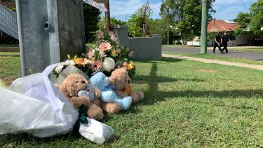 Floral tributes and teddy bears placed near the scene.