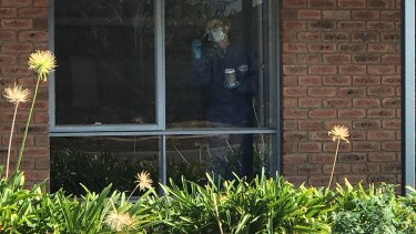 Forensic police dusting for prints at the vacant home next door.