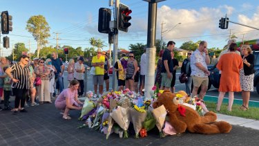 Locals gather for a community vigil at the Alexandra Hills intersection, the day after the crash.