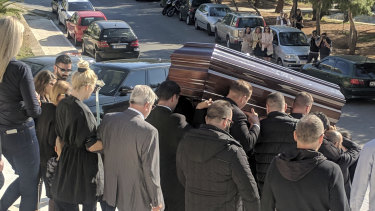 John Macris' coffin leaves the church, with widow Viktoria Karyda following.