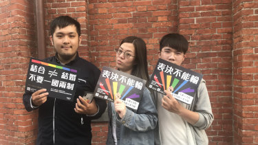 Zhang Jie, left, with friends outside Taipei's Red House after the Taiwanese Parliament voted to legalise same-sex marriage.